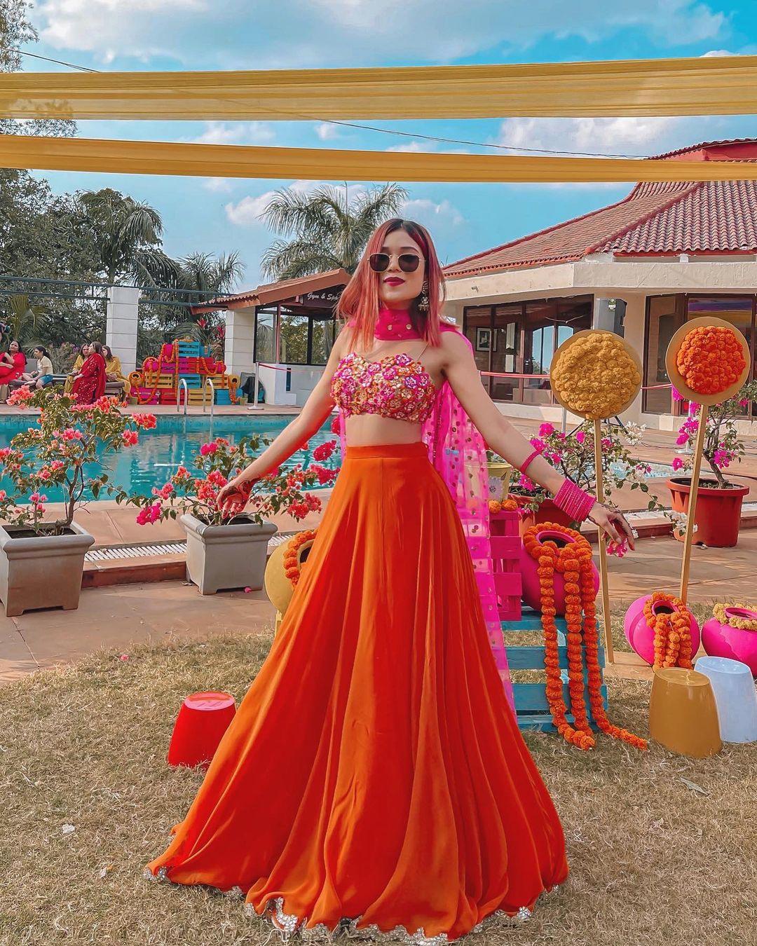 Riya Jain also knows as caughtinacuff looking ethereal in orange and pink lehenga.